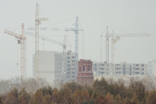 Nowe budynki i żurawie podczas śnieżnej pogody.