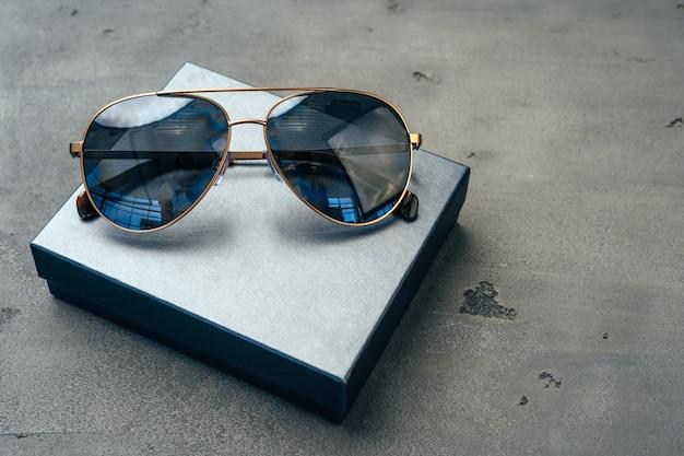 Nowe ciemne okulary aviator na szarym tle betonu z bliska