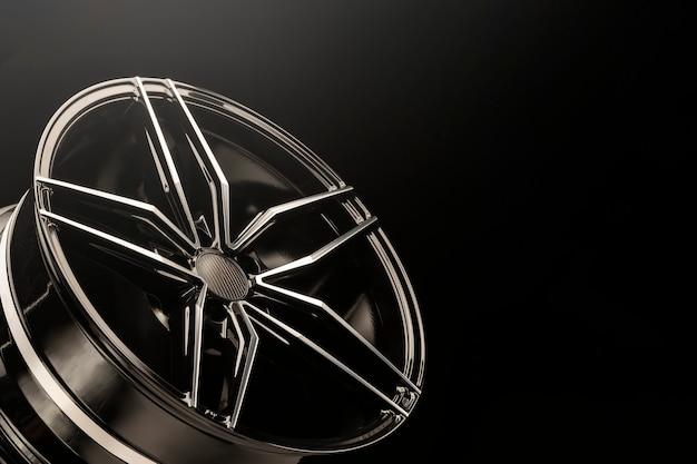 Nowe czarne błyszczące felgi aluminiowe. światło z góry, copyspace.