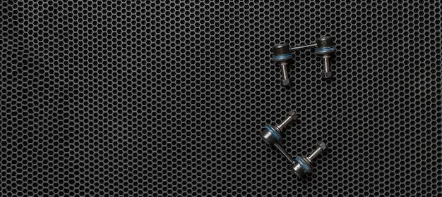Nowe części zamienne do samochodów, detale zawieszenia, ramiona izolowane na ciemnym tle flat lay