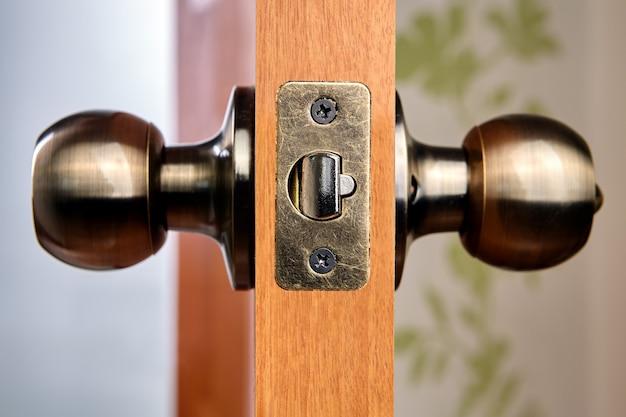 Nowe drewniane drzwi wewnętrzne z klamką i zatrzaskiem z mosiądzu.