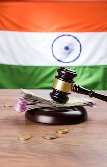Nowe indyjskie banknoty rupii z drewnianym młotkiem przedstawiającym prawo finansowe w indiach z trójkolorowym tłem