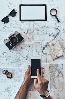 Nowe kierunki. zamknij widok z góry człowieka za pomocą smartfona z okularami przeciwsłonecznymi, aparatem fotograficznym, kompasem,