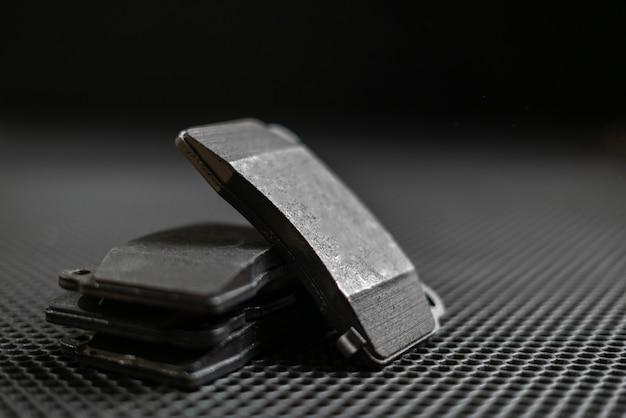 Nowe klocki hamulcowe do samochodów sportowych na płaskim ciemnym tle