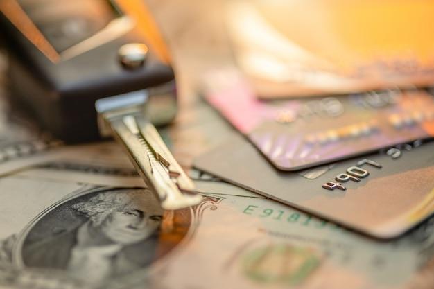 Nowe kluczyki do samochodu, karty kredytowej i banknotu dolara amerykańskiego na drewnianym stole. zakup samochodu lub koncepcja wynajmu samochodu