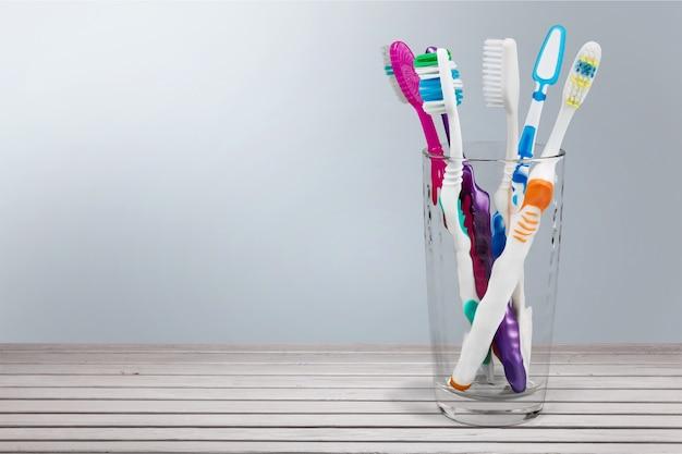 Nowe kolorowe szczoteczki do zębów w szklance na tle