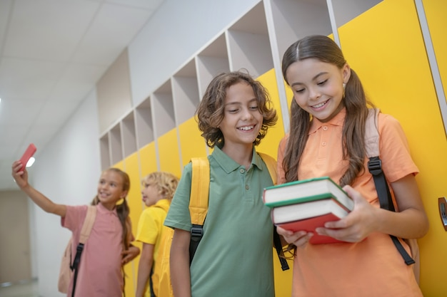 Nowe książki. śliczna dziewczyna pokazuje swoje książki chłopcu w zielonej koszulce