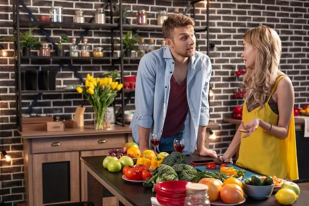 Nowe mieszkanie. dziewczyna i chłopak czują się szczęśliwi gotując obiad i pijąc wino w swoim nowym mieszkaniu
