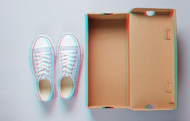 Nowe modne trampki i puste kartonowe pudełko na szaro