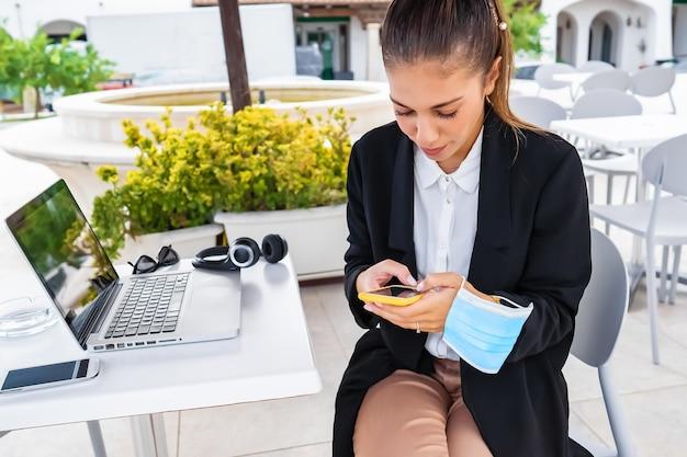 Nowe, normalne, niezależne prace mobilne umożliwiają pracę w dowolnym miejscu z połączeniem internetowym. nowoczesna tysiącletnia hipster kobieta za pomocą smartfona i laptopa przy stole barowym w mieście w masce ochronnej