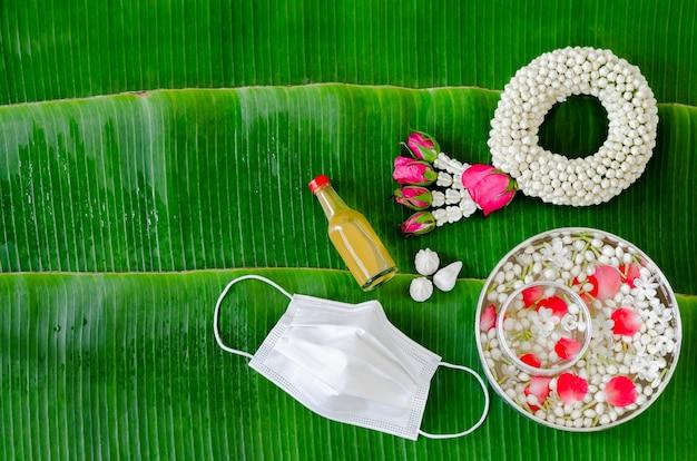 Nowe normalne tło festiwalu songkran z maską na twarz, girlandą jaśminu i kwiatami w misce na wodę
