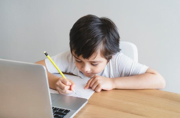 Nowe normalne życie school kid używa komputera do odrabiania lekcji. koncepcja edukacji online e-learning