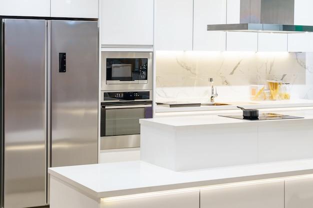 Nowe nowoczesne, jasne, czyste, kuchenne wnętrze z urządzeniami ze stali nierdzewnej w luksusowym domu