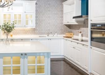 Nowe nowoczesne, jasne, czyste wnętrze kuchni z urządzeniami ze stali nierdzewnej w luksusowym domu
