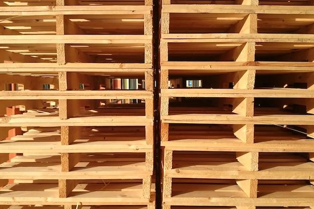 Nowe palety drewniane są układane w magazynie przedsiębiorstwa dostarczającego ładunki.
