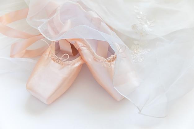 Nowe pastelowe beżowe baletki z satynową wstążką i tututową spódnicą na białym stole