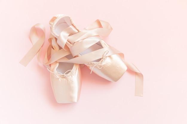 Nowe pastelowe beżowe baletki z satynową wstążką na różowym stole