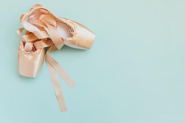 Nowe pastelowe beżowe baletki z satynową wstążką odizolowane na niebiesko