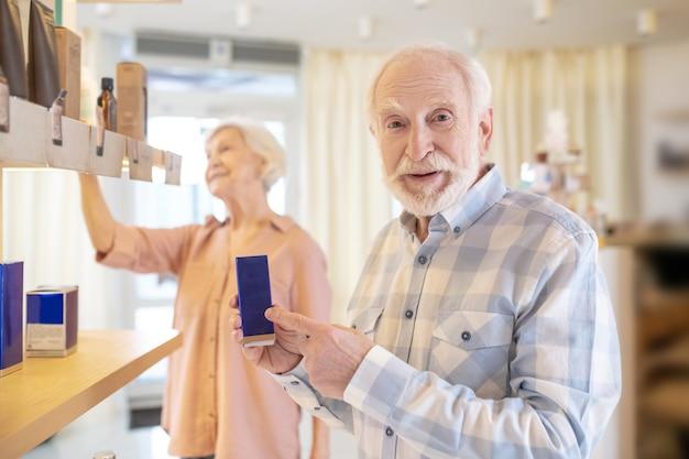 Nowe perfumy. podekscytowana para starszych w salonie piękności