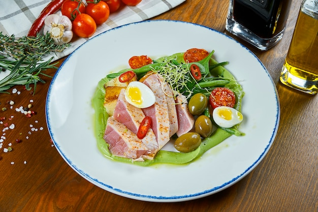 Nowe podejście szefa kuchni do sałatki nicoise ze świeżymi pomidorami, szparagami, papryką chili, oliwkami, jajkami przepiórczymi i smażonym tuńczykiem. tradycyjna francuska sałatka. zamyka w górę widoku na zdrowej owoce morza sałatce
