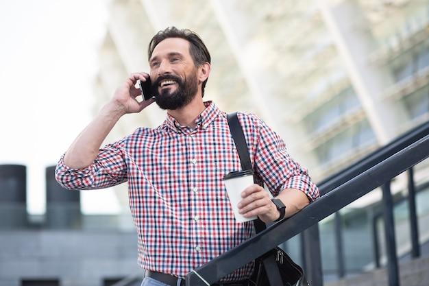 Nowe połączenie. wesoły brodaty mężczyzna rozmawia przez telefon, stojąc na ulicy