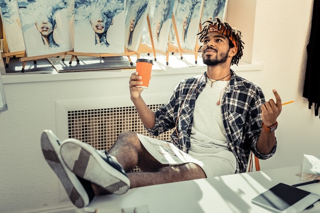 Nowe pomysły. młody nowoczesny przystojny artysta z dredami czuje się emocjonalnie, mając nowe pomysły