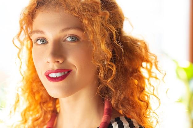 Nowe pomysły. niebieskooka bizneswoman z mosiężnymi włosami uśmiecha się i ma nowe pomysły