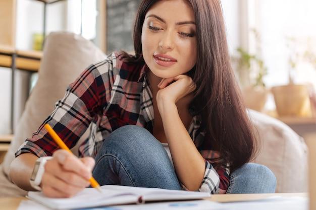 Nowe pomysły. zachwycona atrakcyjna, kreatywna kobieta trzymająca ołówek i zauważająca coś, trzymając ją za brodę