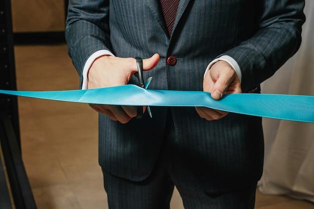 Nowe przedsięwzięcie biznesowe, otwarcie, cięcie niebieskiej wstążki z bliska nożyczkami.