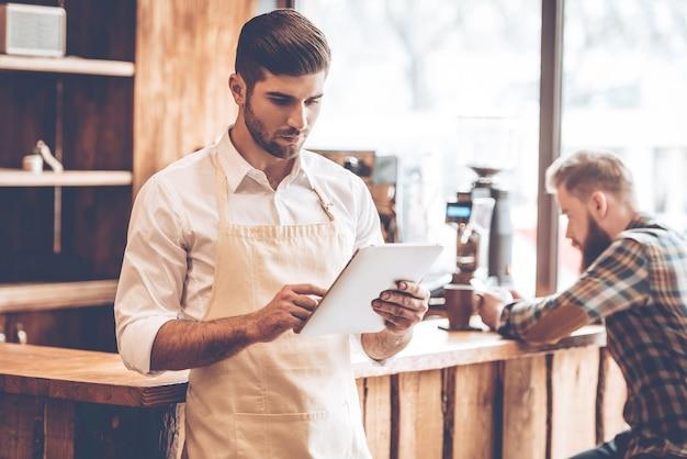 Nowe rozwiązania dla jego biznesu. młody przystojny mężczyzna w fartuchu przy użyciu cyfrowego tabletu stojąc w kawiarni z klientem w tle