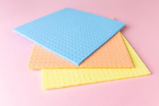 Nowe szmaty do czyszczenia na mokro. niebieskie, żółte i pomarańczowe szmaty na różowo.