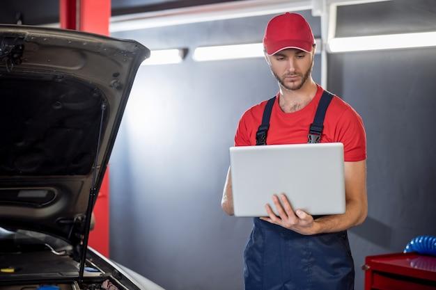 Nowe technologie. młody dorosły mężczyzna atrakcyjny w kombinezonie patrząc na laptopa trzymając w rękach stojących w pobliżu samochodu w warsztacie