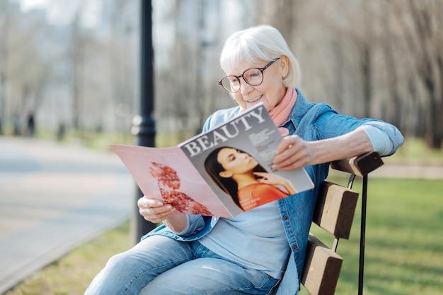 Nowe trendy. uśmiechnięta blond kobieta czyta magazyn siedząc na ławce