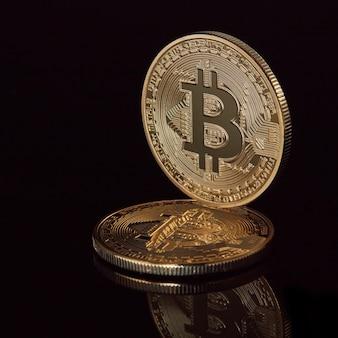 Nowe wirtualne pieniądze ułożone w kryptowaluty złote monety bitcoin na czarnej powierzchni odblaskowej