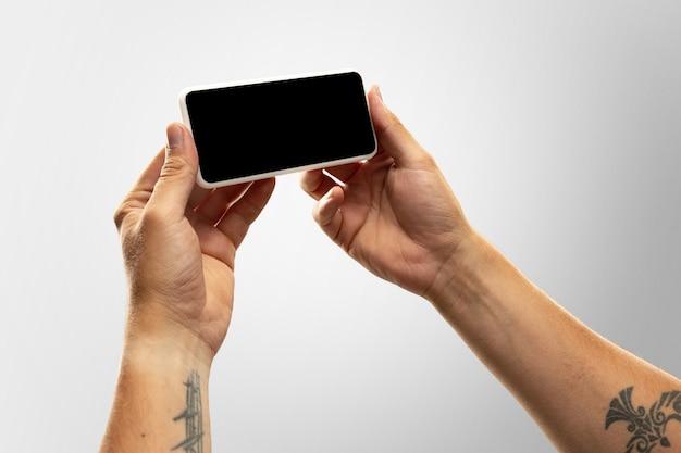 Nowe zasady bezpieczeństwa. bliska męskie ręce trzymając telefon z pustego ekranu podczas oglądania online popularnych meczów sportowych, mistrzostw. miejsce na reklamę. koncepcja urządzeń, gadżetów, technologii.