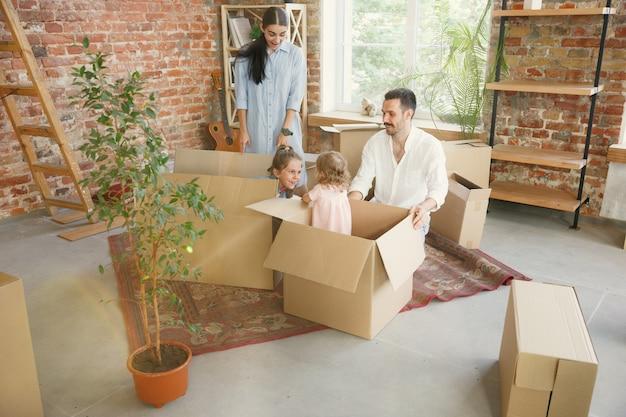 Nowe życie. dorosła rodzina przeprowadziła się do nowego domu lub mieszkania. małżonkowie i dzieci wyglądają na szczęśliwych i pewnych siebie. przeprowadzka, relacje, nowa koncepcja życia. rozpakowywanie pudeł z ich rzeczami, wspólna zabawa.