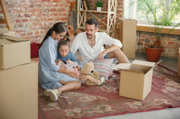 Nowe życie. dorosła rodzina przeprowadziła się do nowego domu lub mieszkania. małżonkowie i dzieci wyglądają na szczęśliwych i pewnych siebie