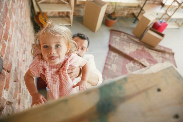 Nowe życie. młody ojciec i jego córka przeprowadzili się do nowego domu lub mieszkania. wyglądaj szczęśliwie i pewnie