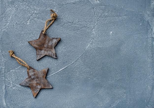 Nowego roku lub bożych narodzeń tło i tekstura. zabawkarskie nieociosane drewniane gwiazdy nad grunge popielatą powierzchnią, odgórny widok
