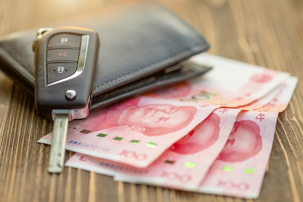 Nowi kluczyki do samochodu z chińskim banknotem na drewnianym stole. zakup samochodu lub koncepcja wynajmu samochodu