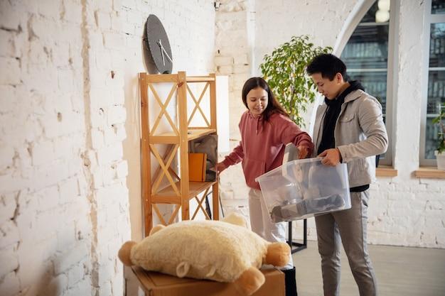 Nowi właściciele nieruchomości, młoda para przeprowadzająca się do nowego domu, mieszkania, wyglądają na szczęśliwych