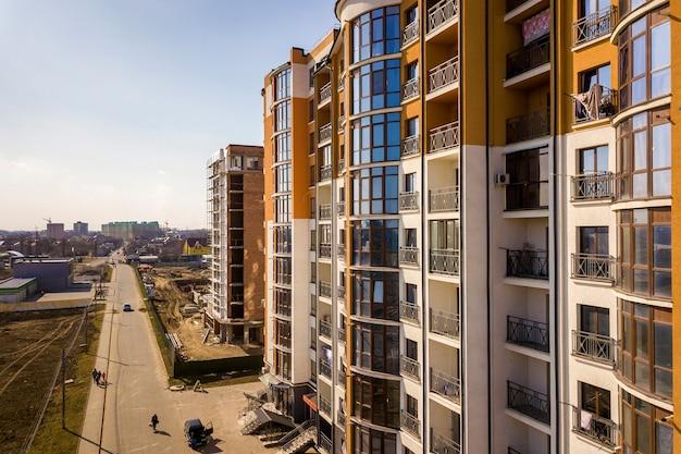 Nowi wysocy budynki mieszkaniowi, parkujący samochody i przedmieście domy na niebieskie niebo kopii interliniują tło.