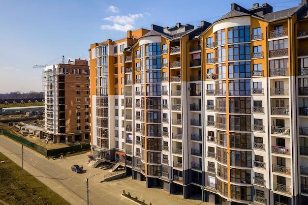 Nowi wysocy budynki mieszkaniowi, parkujący samochody i przedmieście domy na niebieskie niebo kopii przestrzeni