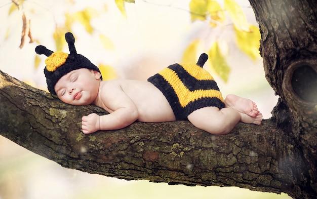 Nowo narodzona dziewczynka ubrana jak pszczoła.