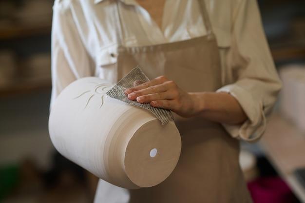 Nowo wykonane. kobieta garncarz trzymająca w rękach nowo wykonane garnki