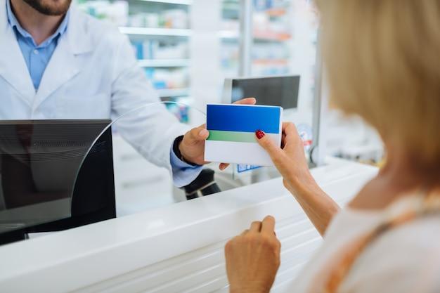 Nowoczesna apteka. kompetentny aptekarz noszący mundur podczas konsultacji z klientem