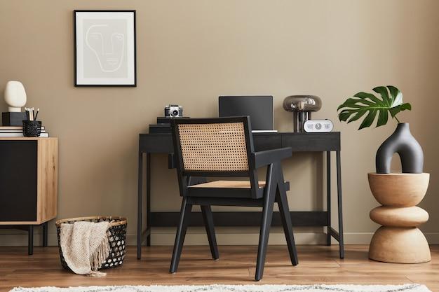 Nowoczesna aranżacja wnętrz biurowych ze stylowym krzesłem, biurkiem, komodą, czarną makietą plakatową, laptopem, książką, organizerem biurowym i eleganckimi dodatkami do wystroju domu. szablon.