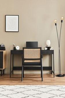 Nowoczesna aranżacja wnętrz biurowych ze stylowym krzesłem, biurkiem, komodą, czarną makietową ramą plakatową, laptopem, książką, artykułami biurowymi i eleganckimi dodatkami do wystroju domu. szablon.