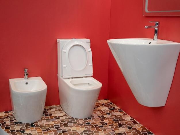 Nowoczesna aranżacja wnętrz domowej łazienki z białą umywalką, toaletą, bidetem
