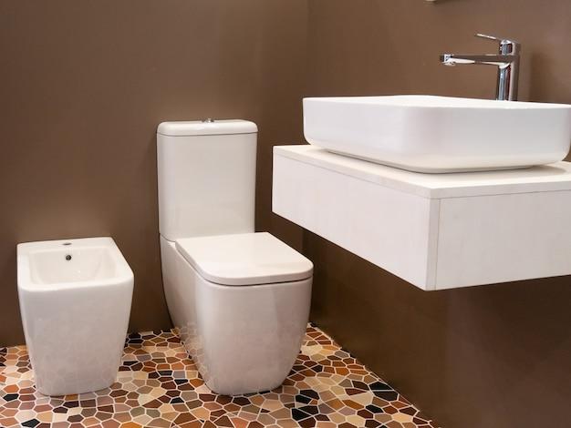 Nowoczesna aranżacja wnętrza łazienki hotelowej z umywalką, toaletą i bidetem.